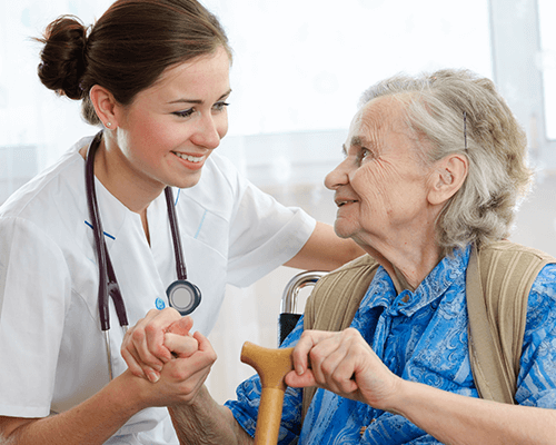 A happy elderly woman holding hand with a caring young nurse.