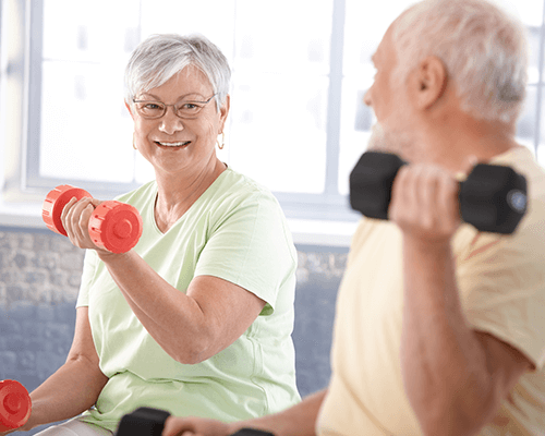 A happy elderly woman working out while smiling and looking at an elderly man also exercising close by in the foreground.