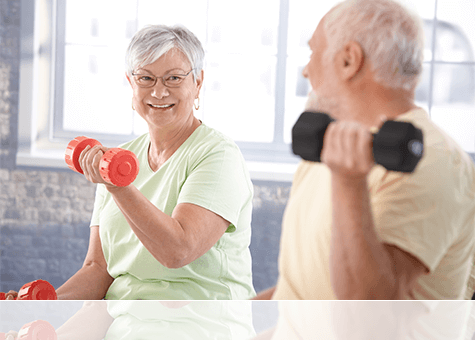 A happy elderly woman working out while smilling and looking at an elderly man also exercising close by in the foreground.
